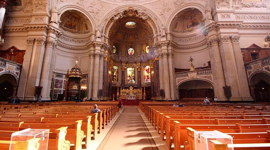 interior de la catedral de berlin. es una nave enorme muy bien iluminada. se ven unas 10 personas muy distanciadas entre si.