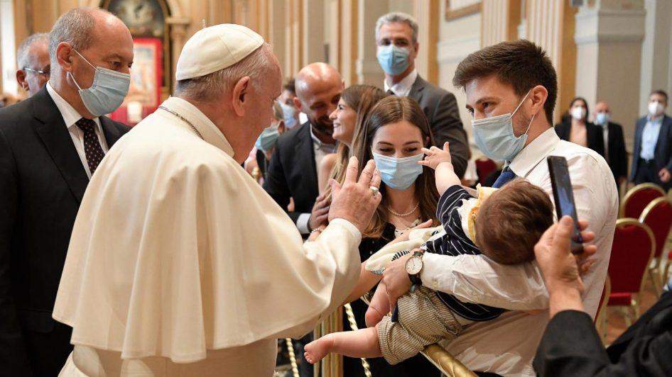 francisco durante el saludo a los familiares en la audiencia con los diaconos. el papa conversa, a traves de una valla, con una pareja joven, el hombre sostiene en brazos al bebe mientras atiende a francisco. la mujer mira al bebe, que se estira