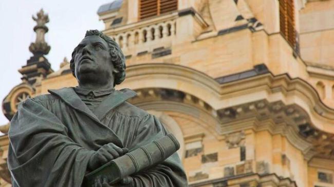 vista parcial en contrapicado de la estatua de martin lutero en Wittenberg. con la biblia en mano, lutero apoya su puño en la tapa y mira al cielo. al fondo se ve la catedral