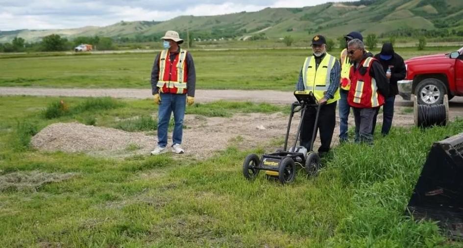 en una zona suburbana, 5 hombres trabajan en la busqueda de tumbas. uno de ellos lleva un radar de profundidad, una especie de maquina cortacesped