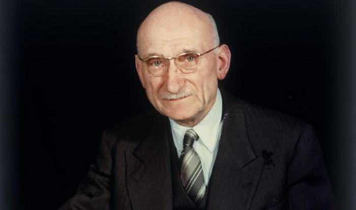 retrato de schuman, levemente sonriente, casi con una muesca. un hombre mayor, casi calvo, lleva lentes al aire y viste traje oscuro y corbata en franjas inclinadas. el fondo de la foto es totalmente negro.