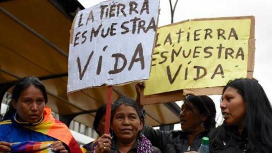 cinco mujeres qom manifestando por la tierra. parecen estar en una parada de omnibus. son de mediana edad, visten ropa urbana estandar y llevan carteles escritos a mano, que dicen: la tierra es nuestra vida