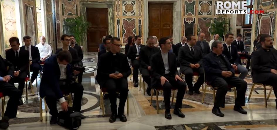 seminaristas escuchando al papa. estan sentados en sillas separadas, todos con vestimenta formal, algunos con clerigman.