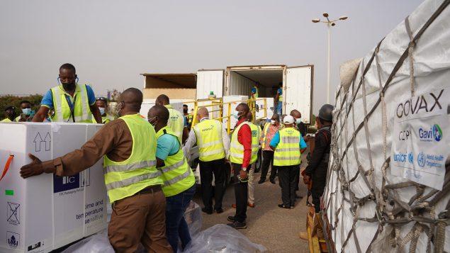 llegada de las primeras vacunas a Ghana. funcionarios del aeropuerto cargan las cajas en camiones. se ven logos de covax y unicef.
