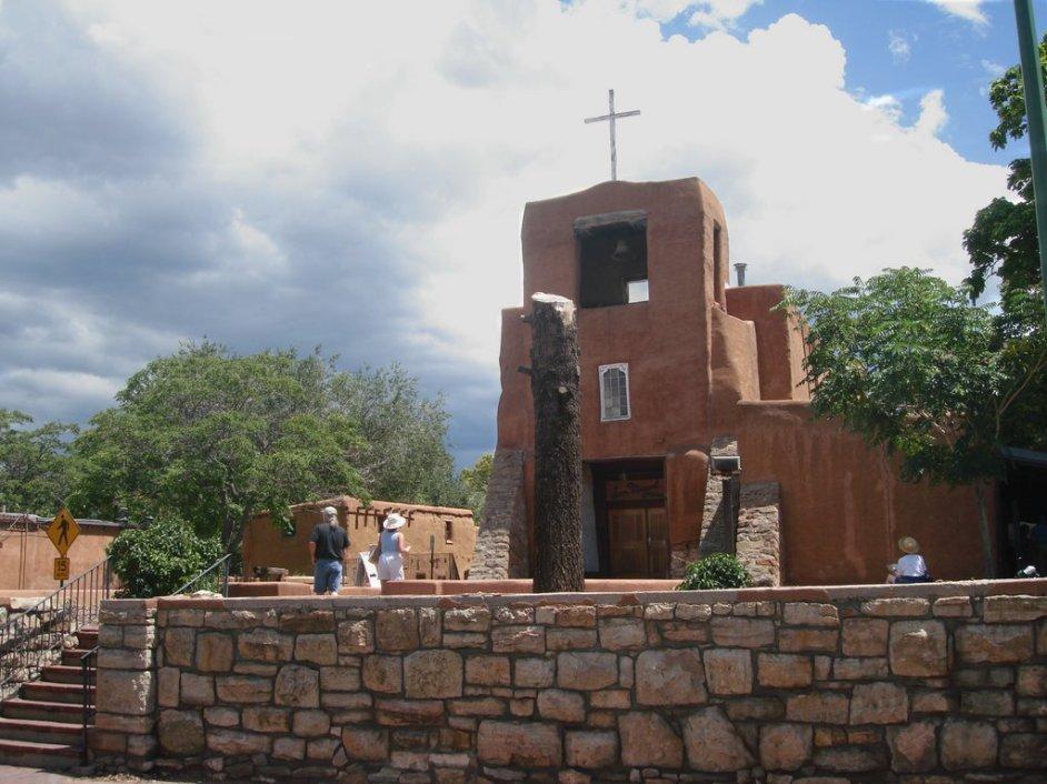vista de la fachada de la primera capilla establecida en estados unidos, en nuevo mexico. es de arquitectura (aunque reconstruida) de la epoca colonial, se aprecia el campanario y una cruz sencilla encima de la torre. dos personas caminan por la explanada.