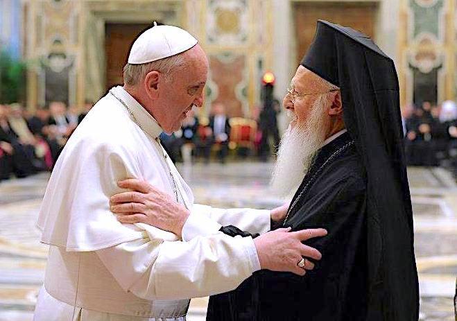 francisco y bartolomeo se saludan tomados de los brazos. el papa viste de blanco y el patriarca, que parece mayor y lleva barba blanca, viste de negro. el fondo esta muy difuso, se distingue gente sentada como en un gran semicirculo.