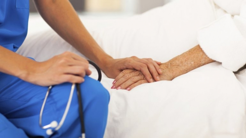una integrante del equipo de salud toma la mano de una paciente mayor que esta acostada. solamente se ven las manos, la tecnica tiene un estetoscopio sobre su regazo.