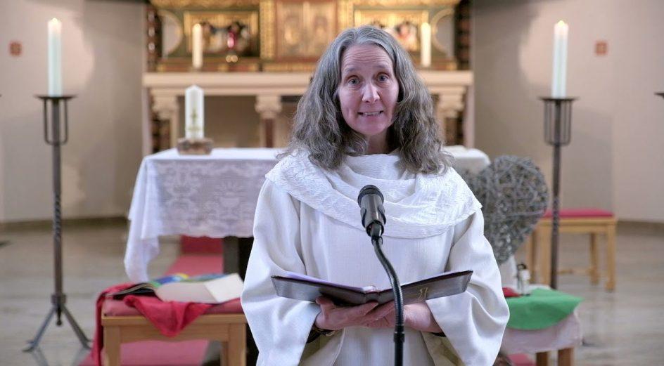 la párroca sandra, usando un alba, está hablando durante una celebracion. detras se aprecia el altar, sencillo y con las velas encendidas. ella es de mediana edad, y lleva el cabello largo y suelto y de color gris