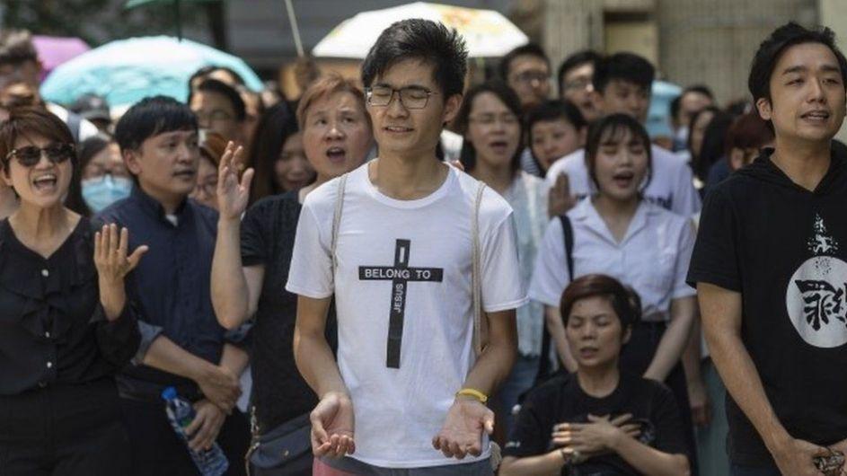 cristianos manifiestan cantando por las calles de hong kong. en primer plano, un hombre joven con las palmas abiertas y ojos cerrados. lleva una camiseta blanca con una cruz negra que dice en su interior: pertenezco a jesus, en ingles.