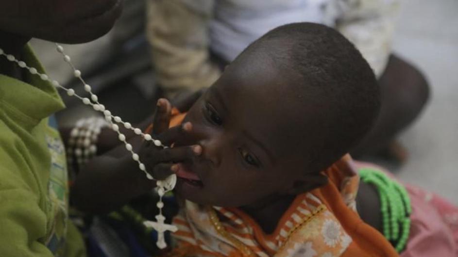 primer plano de una mujer nigeriana con un bebe en brazos. ambos llevan ropas coloridas, la joven usa un rosario al cuello, que el bebe se lleva a la boca, con la mirada distraida.