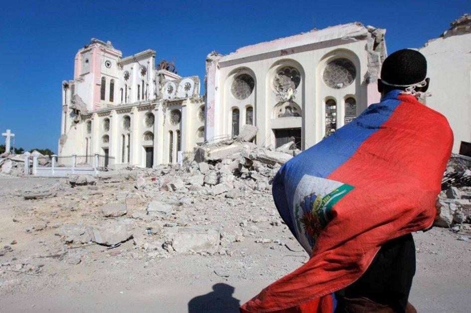 un joven haitiano contempla desde lejos un templo muy afectado por el terremoto. va envuelto en la bandera de su pais.