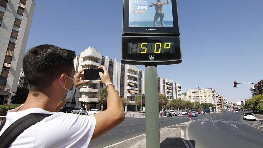 un muchacho toma una fotografia con su celular, apuntando a un termometro urbano en medio de una ciudad espaniola. el aparato marca 50 grados