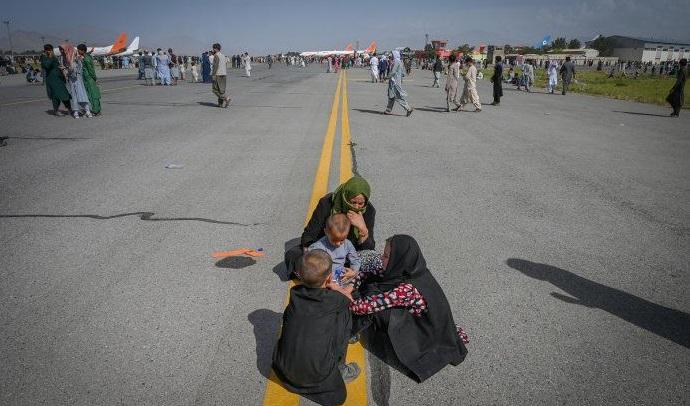 dos mujeres afganas sentadas en una de las pistas del aeropuerto, con ellas dos niños chicos. a lo lejos se ven aviones comerciales y muchas personas caminando por la pista, en todas direcciones.