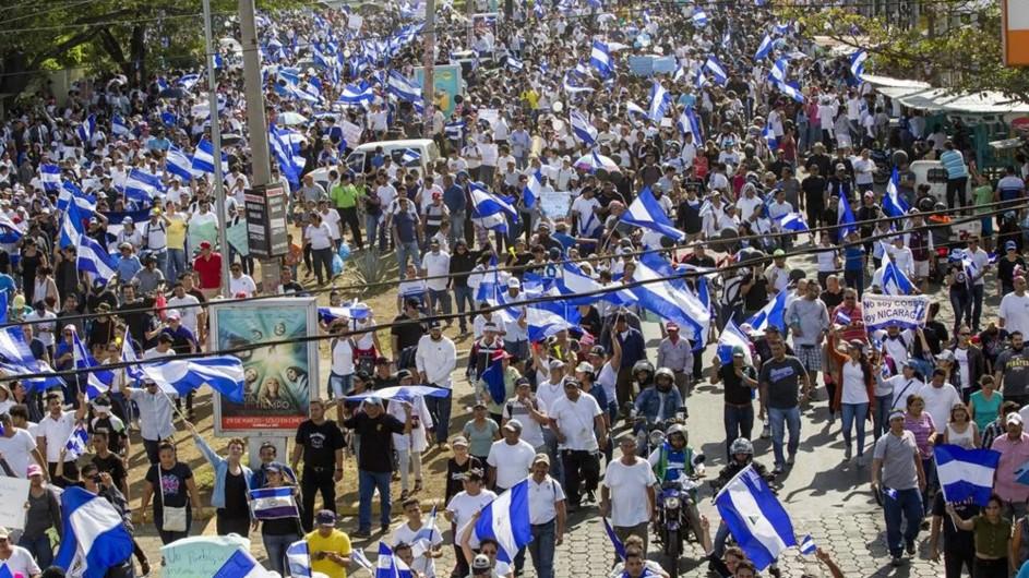 panoramica de una manifestacion callejera en nicaragua. es un mar de gente que ocupa la calle y se pierde en la distancia. abundan las banderas nacionales.