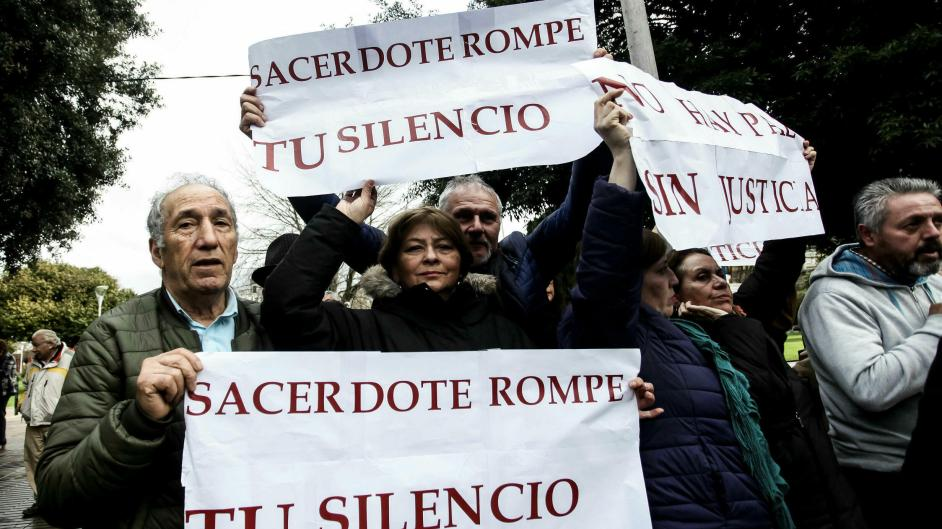 tres mujeres y tres hombres de mediana edad estan protestando con pancartas que dicen: sacerdote rompe tu silencio y no hay paz sin justicia.