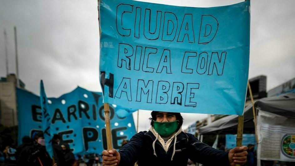manifestantes portan carteles en olla popular de la periferia de buenos aires. uno dice: barrios de pie, el otro, en primer plano, dice: ciudad rica con hambre.