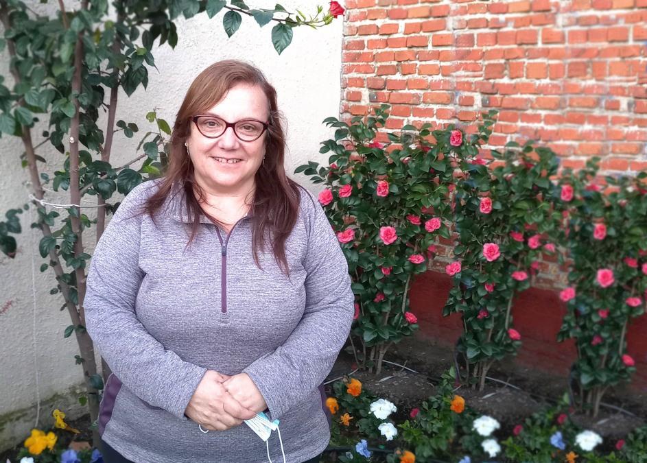 retrato de la entrevistada en el florido jardin de su casa. esta sonriente, lleva cabello largo suelto, usa lentes y tapabocas en mano.
