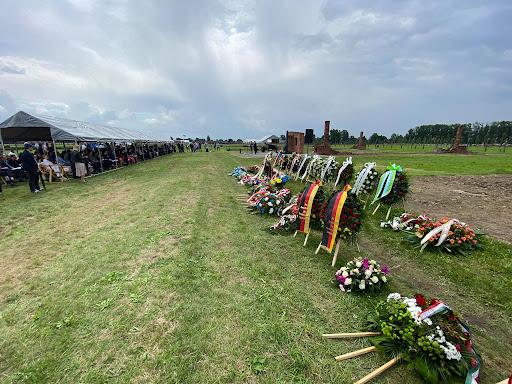 en las afueras del campo de auschwitz, el dia de la conmemoracion. se ven ofrendas florales arregladas en dos filas, muchas tienen banderas de paises europeos. al frente, y a unos 25 metros se encuentra el publico, bajo carpas que protegen del sol.