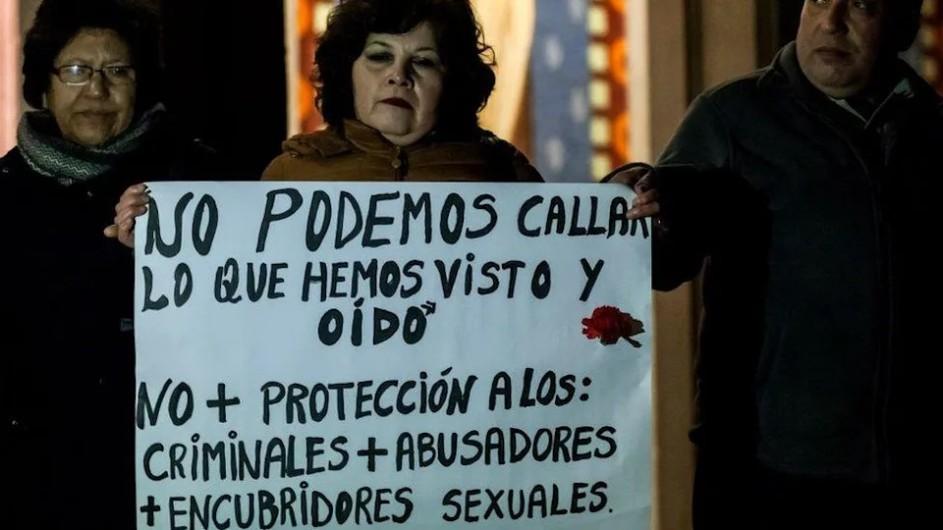 dos mujeres y un hombre tras un cartel que dice: no podemos callar lo que hemos visto y oido. no mas proteccion a los criminales abusadores encubridores sexuales. los tres son de mediana edad, su actitud es calma y sus rostros muy serios.