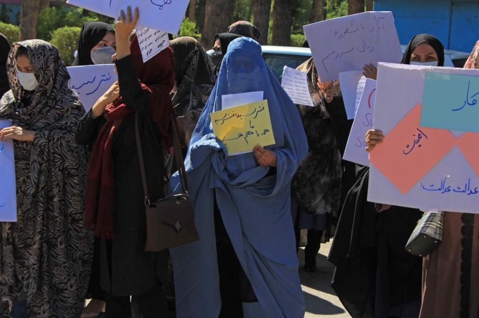 varias mujeres protestan por las calles en afganistan. van cubiertas de pies a cabeza, algunas hasta con velos. llevan carteles en arabe, hechos a mano, que muestran a las camaras..