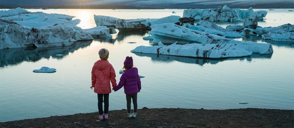 dos nenas tomadas de la mano en la orilla observan un paisaje nevado al atardecer, son trozos de hielo esparcidos, como si se fueran desprendiendo de bloques mayores.