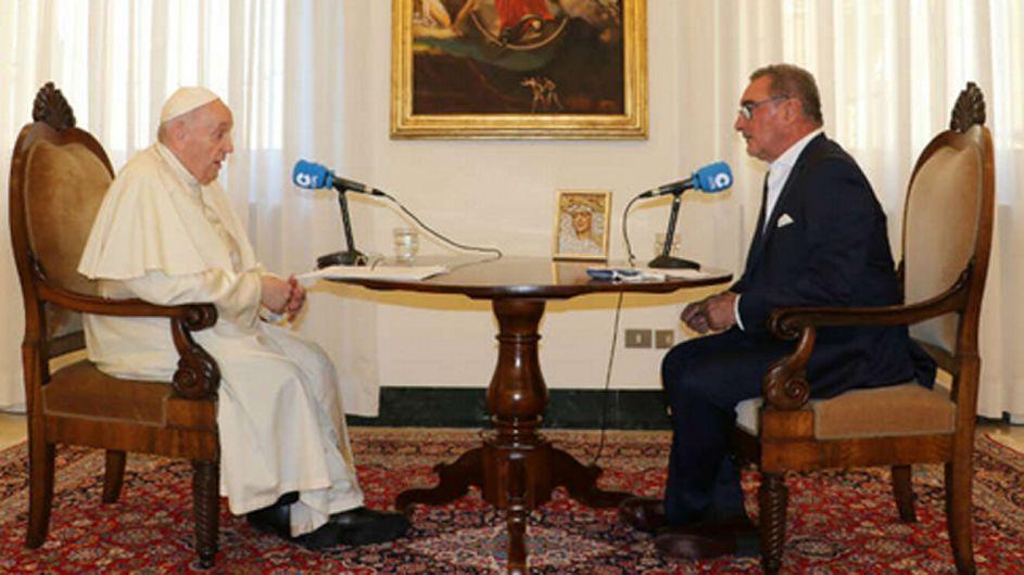 el papa y su entrevistador sentados a una mesa en una sala del vaticano.