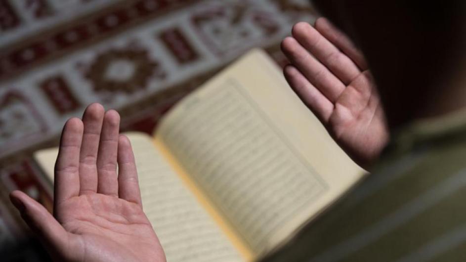 una persona esta orando, con las palmas hacia arriba. abajo y fuera de foco se ve el coran abierto, encima de su soporte.