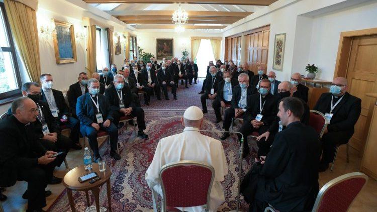 el papa, que esta de espaldas a la camara y sentado en el extremo de un gran salon, tiene enfrente a unos cincuenta jesuitas, todos visten trajes negros y llevan clerigman. a pesar de las mascarillas, se nota que todos prestan atencion