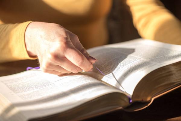 una mujer lee la biblia, que esta en primer plano. sostiene en su mano el hilo que sirve de marcador.