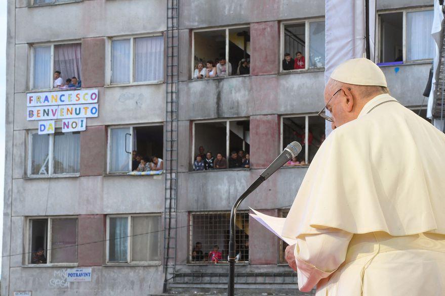 el papa lee de pie frente al microfono en el barrio gitano. al fondo un edificio vetusto y la gente mira por las ventanas. un cartel en italiano le da la bienvenida.