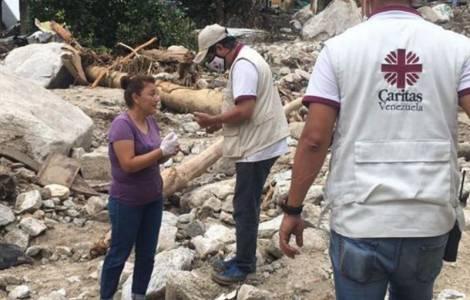 dos voluntarios de caritas, con sus chalecos identificatorios, asisten a una mujer afectada por las inundaciones. al fondo se ven derrumbes causados por el agua.