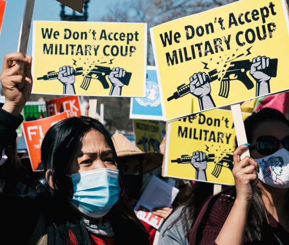 primer plano de dos mujeres en una manifestacion. portan carteles que dicen we don´t accept military coup, y que muestran dos manos rompiendo un fusil
