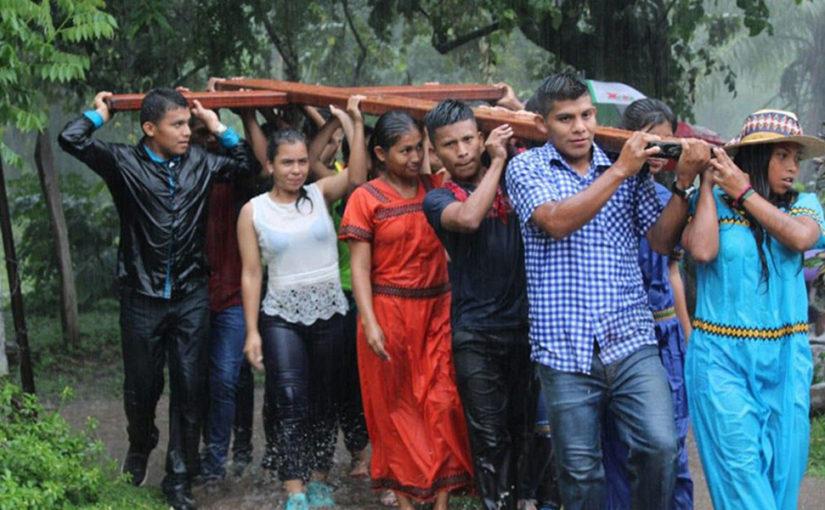 muchachas y muchachos latinoamericanos llevan una enorme cruz de madera al hombro. van por un camino selvatico y estan empapados, por la lluvia intensa que cae.