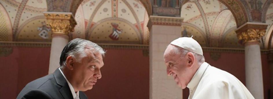 orban y francisco se acercan inclinandose para saludarse. solamente se ven sus cabezas y parte del torso. francisco sonrie, orban no.