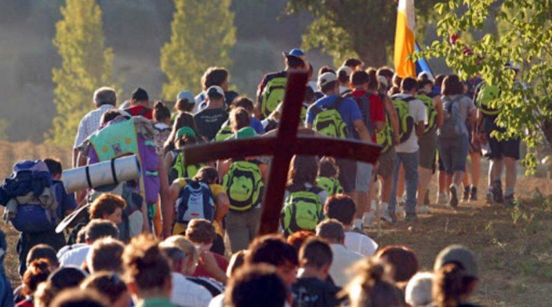 una procesion por un camino rural. son jovenes en su mayoria, la foto esta tomada desde atras, se ven una cruz de madera y una bandera del vaticano. muchos llevan mochilas.