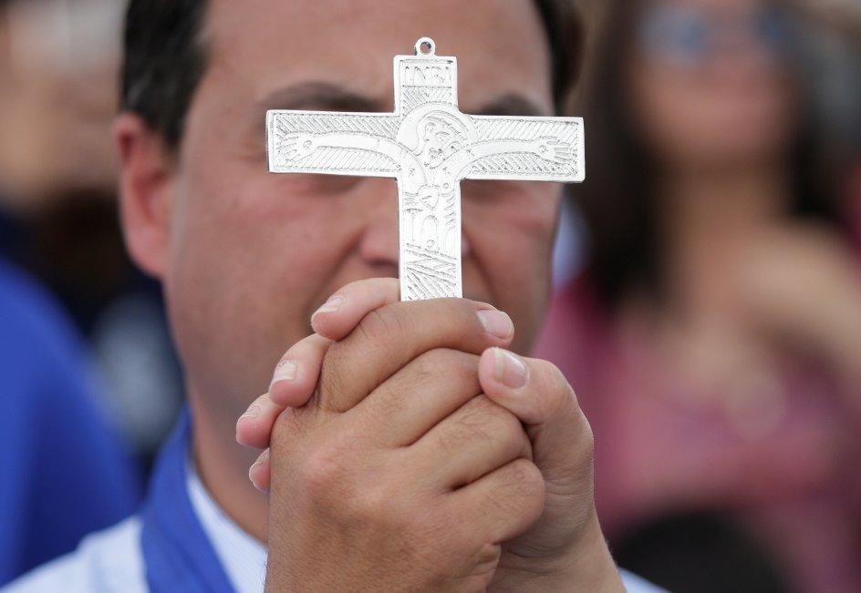 un hombre sostiene una cruz de metal, a la altura de sus ojos. la mano de otra persona sujeta la suya.