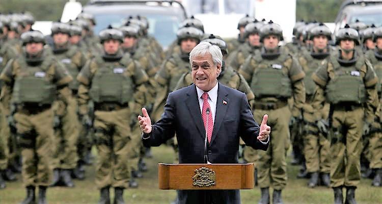 presidente chileno hablando con las manos abiertas, detras un batallon de soldados y equipo belico.