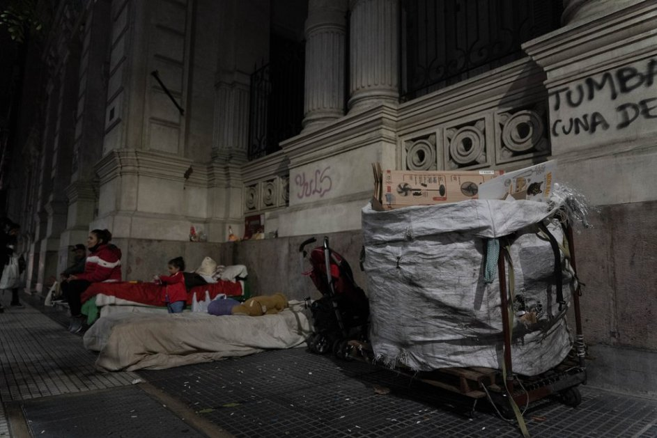 una madre y su hijo chico, viviendo a los pies de un edificio en la capital argentina. al costado de la improvisada cama hay un carro de mano de recoleccion