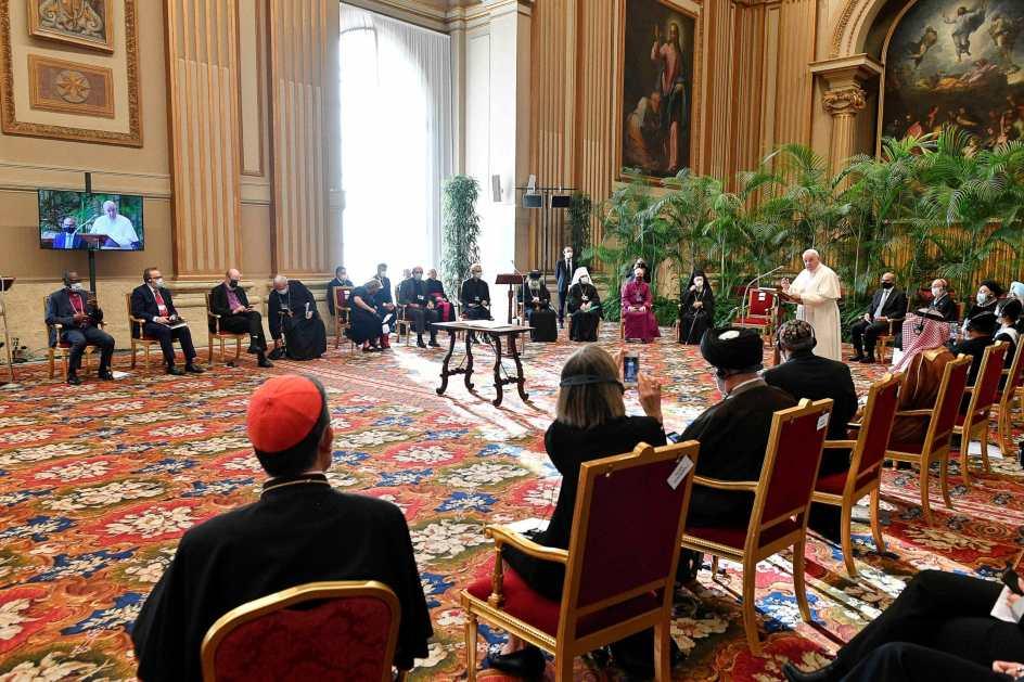 francisco hablando en un salon del vaticano. a su alrededor sentados los lideres religiosos. el salon es muy luminoso y esta decorado con plantas de palma.