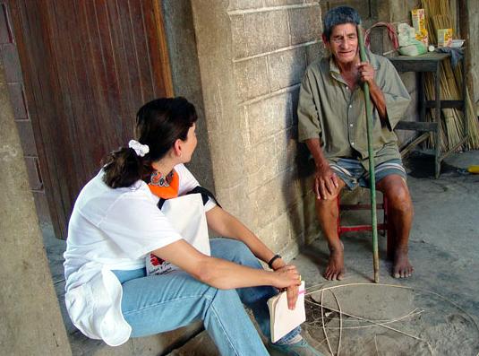 una joven misionera sentada en el umbral conversa con un anciano ciego, que permanece sentado en una vieja silla, los pies descalzos. su baston es un trozo de caña.