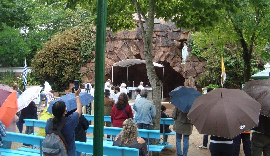 celebracion bajo la lluvia del 11 de febrero en la gruta de lourdes. algunos peregrinos usan paraguas, al fondo se ve el altar, la virgen y el pabellon nacional