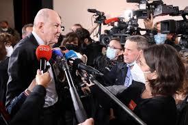 Sauve esta de pie frente a los microfonos, a los periodistas y las camaras. es un hombre mayor, muy alto y de vestimenta formal.
