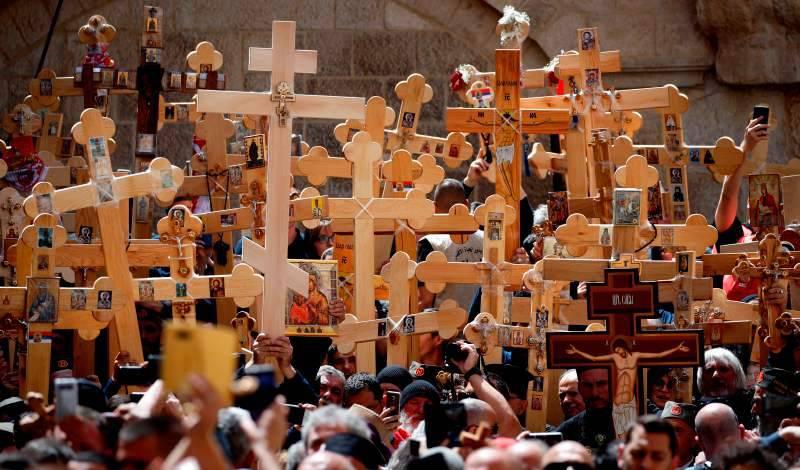 muchas personas en procesión, la mayoría lleva crucifijos altos de madera, que levantan por sobre sus cabezas.