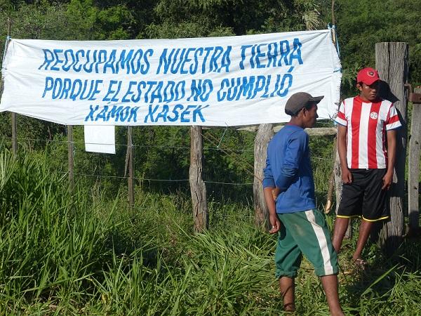 dos muchachos paraguayos -uno de ellos con la camiseta de la seleccion- estan parados junto a un cartel que dice: recuperamos nuestra tierra porque el estado no cumplio. xamok xasek.